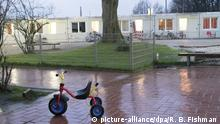 A child's tricycle sits in front of refugee accomodations in Bochum, Germany (picture-alliance/dpa/R. B. Fishman )