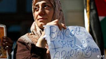 A Palestinian woman hold up a placard reading ' boycott Israel as Aparta regime'