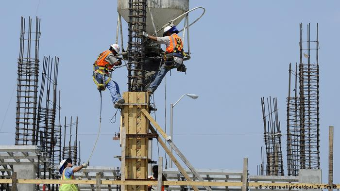 Construction workers pouring concrete into rebar while erecting a new building in Dallas, Texas
