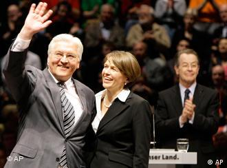 German Foreign Minister Frank-Walter Steinmeier holding his wife in one arm waves to a large crowd at a party conference