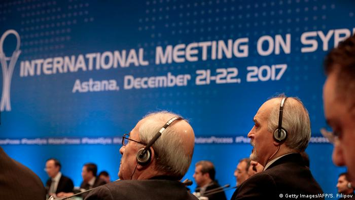 men listen at the Astana Syria talks (Getty Images/AFP/S. Filipov)