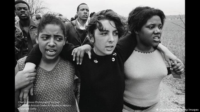 Young women sing freedom songs as they march toward Montgomery, Alabama, during the Selma to Montgomery March for Voting Rights in 1965 (Charles Moore)