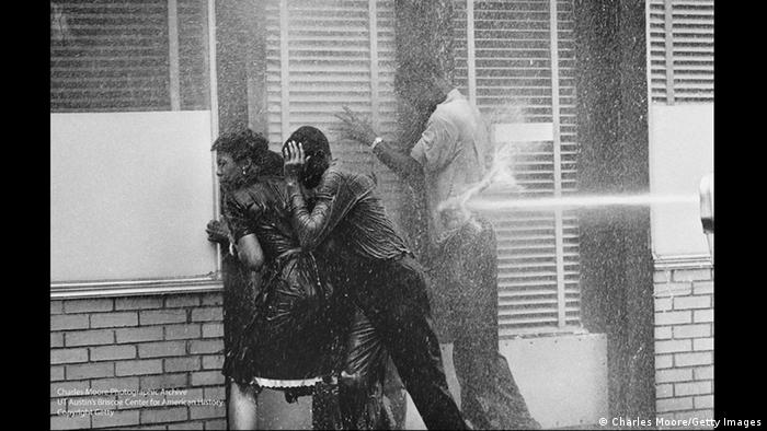 Demonstrators huddled in a doorway seek shelter from hoses turned on them, 1963 (Charles Moore)