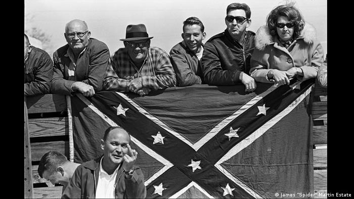 White hecklers confront civil rights marchers from behind a Confederate flag during the Selma to Montgomery March for Voting Rights in 1963 (Spider Martin)