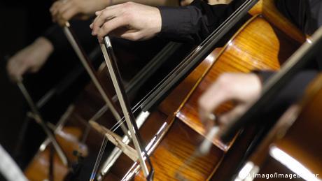Nahaufnahme von Händen, die einen Bogen halten und Cello spielen.