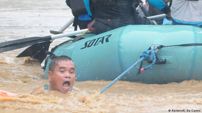 A man clings to the rope of a rescue boat in raging floodwaters.