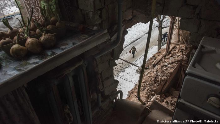 A local resident is seen through a hole in an bombed apartment building