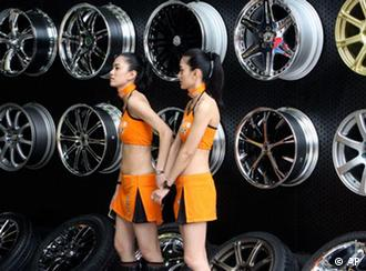 Models stand in front of wheels at Dunlop exhibition booth at the Shanghai International Auto Show on its opening day, Monday, April 20, 2009 in Shanghai, China. World automakers were launching 13 new models Monday as they converged on China's commercial capital for the show, a key showcase for the only major growing car market. (AP Photo/Eugene Hoshiko)