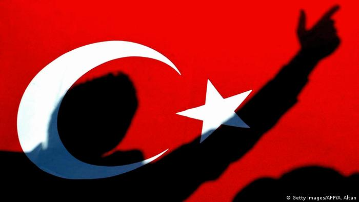 The shadow of a man, with his arm outstretched and his fingers creating the image of a gun, is pictured on a Turkish flag.