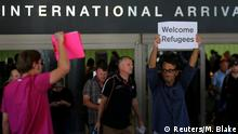 ARCHIV Juni 2017 *** FILE PHOTO: Retired engineer John Wider, 59, is greeted by a supporter of U.S. President Donald Trump as he holds up a sign reading Welcome Refugees at the international arrivals terminal at Los Angeles International Airport in Los Angeles, California, U.S. on June 29, 2017. REUTERS/Mike Blake/File Photo