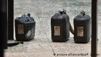 Three petrol canisters, partly deformed by heat, among glass shards