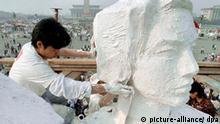 Kunststudenten errichten am 30.5.1989 auf dem Platz des Himmlischen Friedens (Tien An Men) in Peking als Symbol der Demokratiebewegung eine Nachbildung der amerikanischen Freiheitsstatue. Im Hintergrund rechts die Große Halle des Volkes, in der Mitte das Denkmal der Volkshelden. Die Proteste hatten mit dem Tod des in Ungnade gefallenen Chefs der Kommunistischen Partei Chinas, Hu Yaobang, am 15. April 1989 begonnen. Studenten strömten zum Platz des Himmlischen Friedens ums Kränze niederzulegen. Die Trauer verwandelte sich in eine Bewegung, die Millionen von Chinesen gegen Korruption und für Demokratie mobilisierte. Am 3. Juni 1989 werden die Proteste durch den Einsatz von Militär blutig beendet. In einem grauenvollen Blutbad auf dem Tien-an-Men-Platz in Peking sterben unzählige Menschen, vermutlich mehr als tausend. Die genaue Zahl der Opfer bleibt unbekannt.