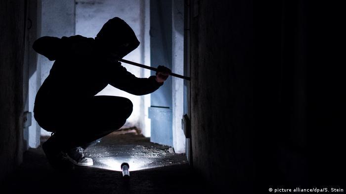 Silhueta de indivíduo arrombando porta com pé-de-cabra, à luz de lanterna