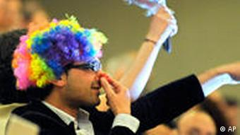 A demonstrator dressed as a clown cries from the media tribune against Iranian President Mahmoud Ahmadinejad during his speach during the opening of the Durban Review Conference (UN's Conference against Racism) at the European headquarters of the United Nations, UN, in Geneva, Switzerland, Monday, April 20, 2009