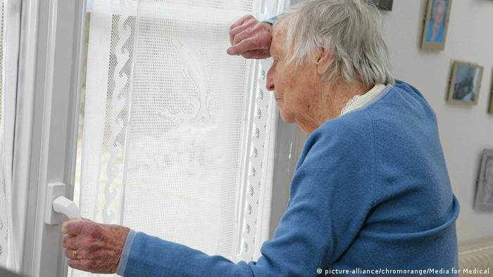 An older woman stares out of a window
