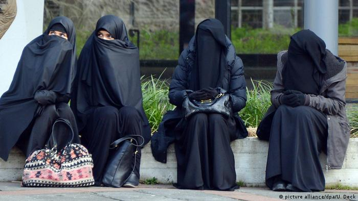 Vier verschleierte Frauen sitzen auf einem Mäuerchen (Foto: picture alliance/dpa/U. Deck)