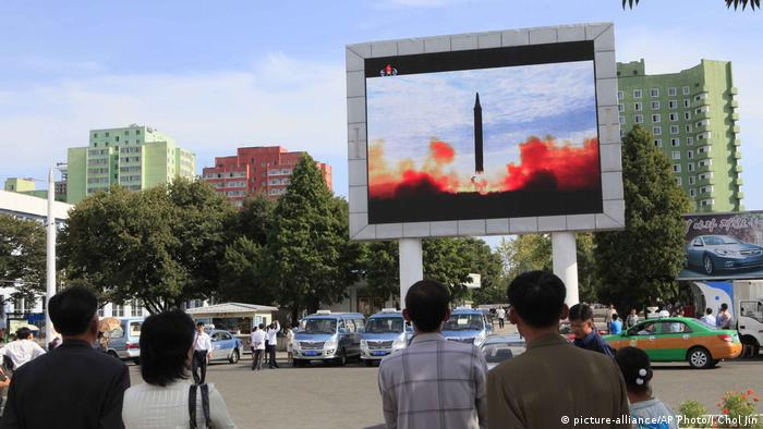 People watch a launching of a Hwasong-12 strategic ballistic rocket aired on a public TV screen
