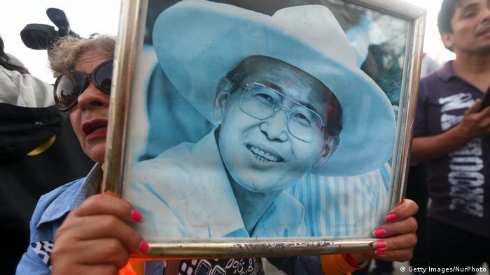 Una manifestante sostiene una fotografía de Alberto Fujimori.