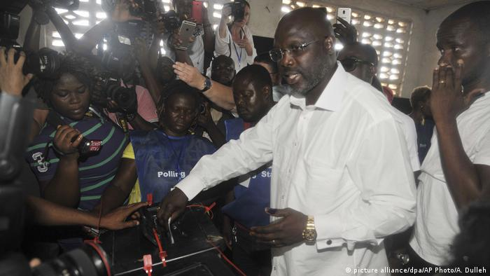 George Weah casting his ballot at the presidential elections in 2017 while journalists and camera men are watching (picture alliance/dpa/AP Photo/A. Dulleh)