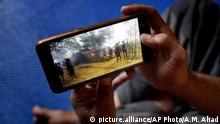In this Dec. 23, 2017 photo, Mujibullah, 22, a Rohingya refugee watches a video, which he has shot in Myanmar before crossing over into Bangladesh, at Kutupalong refugee camp in Ukhiya, Bangladesh. For many Rohingya living in refugee camps in Bangladesh, all that remains of their old lives in Myanmar are memories captured in photos and videos on their cellphones. Since August, more than 630,000 Rohingya Muslims have fled to Bangladesh to escape attacks by Myanmar security forces. Few refugees had the chance to grab many belongings when they fled, but most took their cellphones. (AP Photo/A.M. Ahad) |