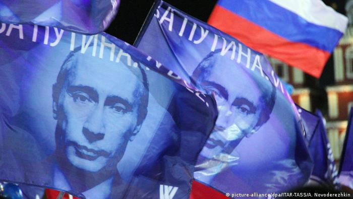 Vladimir Putin's supporters wave flags bearing his face