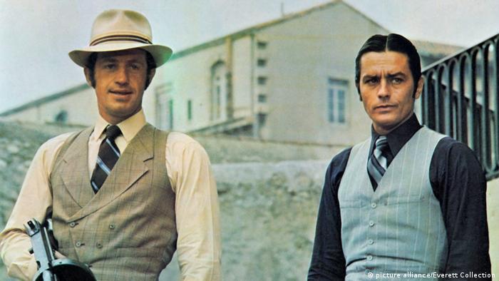 Belmondo mit Hut und Maschinenpistole und Alain Delon. (picture alliance/Everett Collection)