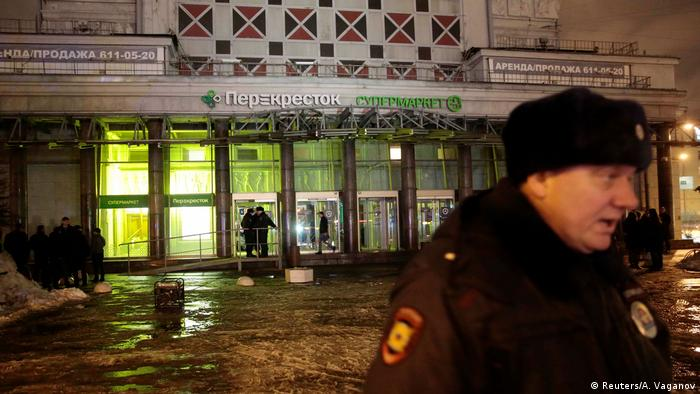 A policeman stands guard near a supermarket after an explosion in St Petersburg