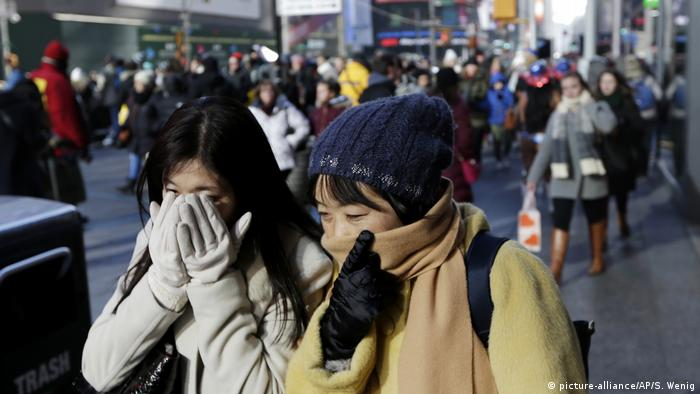 Pedestrians try to keep warm by covering their faces while walking in Times Square, New York