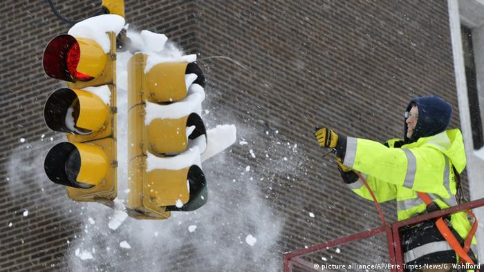 City of Erie traffic engineering employee Chuck Carnes Jr. uses compressed air to clear snow from a traffic signal