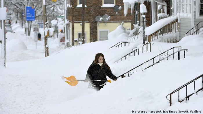 A woman shovels snow from her house entrance