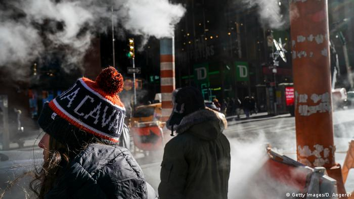 Pedestrians wear winter hats as steam rises from a manhole in Lower Manhattan