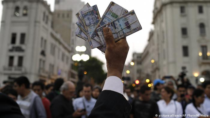 Protesters holds up fake money during an anti-corruption march in Lima, Peru