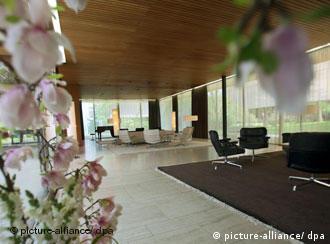 ein riesiger Raum mit großen Fenstern, zwei Sofas und Blumen im Vordergrund
