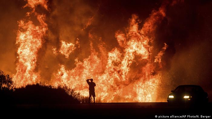 Motorists on Highway 101 watch flames from the Thomas fire leap above the roadway north of Ventura, California in December 2017