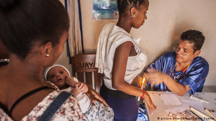 Curandeiro usa velas para tratar paciente na favela de Petare, em Caracas