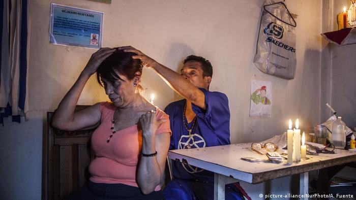 Curandeiro atende paciente no beco dos bruxos, em Caracas