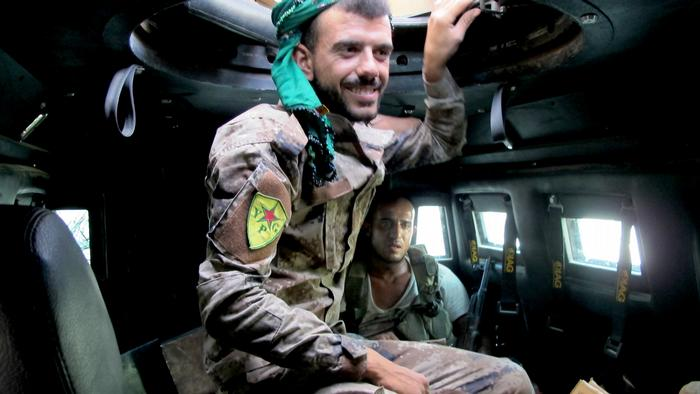 YPG members inside an armed vehicle during Raqqa's operation against IS