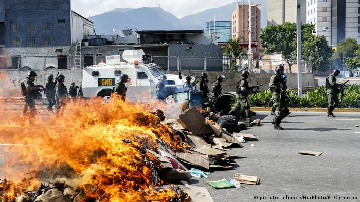 Riot police move past burning barricades in Venezuela (picture-alliance/NurPhoto/R. Camacho)