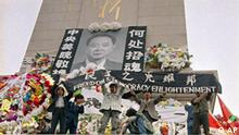 Chinese students hold aloft a banner calling for 'Freedom & Democracy Enlightment' on the martyrs monument in Beijing's Tiananmen Square festooned on Wednesday, April 19, 1990 with a giant portrait of Hu Yaobang. (AP Photo/Mark Avery)