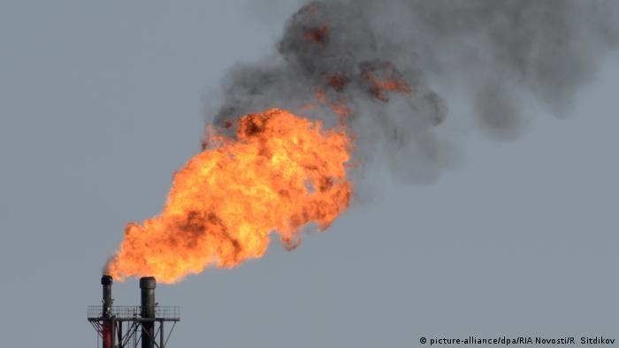 Черный дым уносится в атмосферу от огня, вылетающего из труб