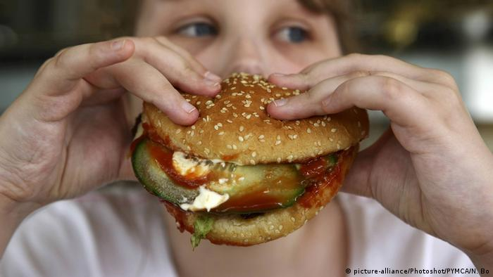 Kind hält Burger in der Hand (picture-alliance/Photoshot/PYMCA/N. Bo)