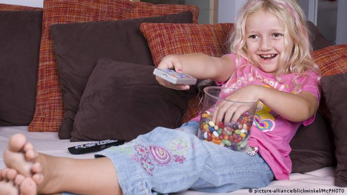 Girl eating sweets holds TV remote control