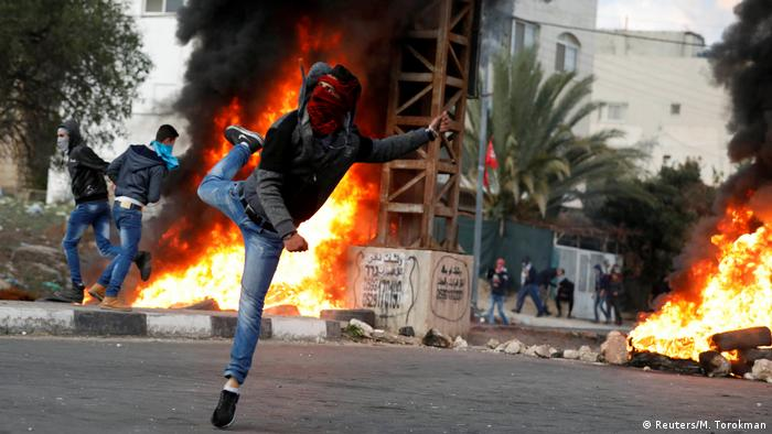 A Palestinian protester in the West Bank hurls stones at Israeli troops as fires burn in the background.