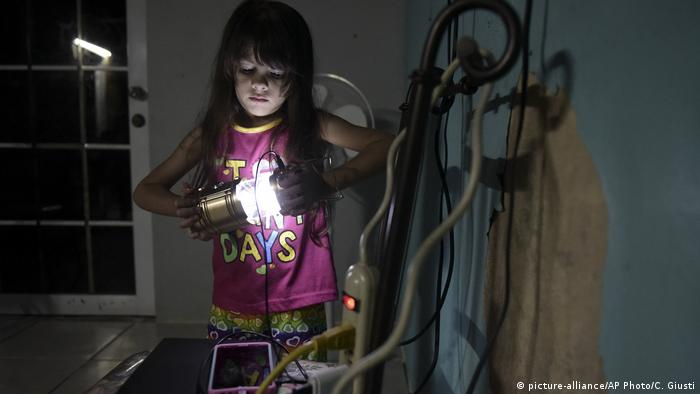 Little girl holds a lantern in a dark room in Puerto Rico in December 2017
