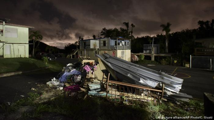 A mountain of rubble remains in front of a house in Morovis, Puerto Rico three months after Hurricane Maria hit (picture-alliance/AP Photo/C. Giusti)