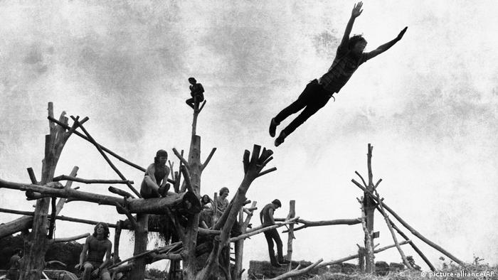 Rock music fans sit on a built wooden structure in Woodstock.  A visitor jumps into a haystack.  (picture-alliance / AP)