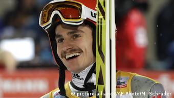Germany's Richard Freitag laughs after his first competition jump
