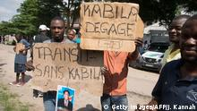 ARCHIVBILD November 2017 *** Opposition supporters hold up placards reading 'Kabila - get lost' and 'Transition without Kabila' as they demonstrate outside the residence of the Union for Democracy and Social Progress party (UDPS - Union pour la democratie et le progres social) leader Felix Tshisekedi in Kinshasa on November 30, 2017, during a day of protest called for by the opposition parties to demand the departure of President Kabila. In power since 2001, Kabila's prolonged rule has already led to street protests and a bloody crackdown. Elections had been due to take place by the end of 2017 under a deal with the opposition aimed at avoiding bloodshed, but the date has since been pushed back until December 2018, further heightening tensions. / AFP PHOTO / JUNIOR KANNAH (Photo credit should read JUNIOR KANNAH/AFP/Getty Images)