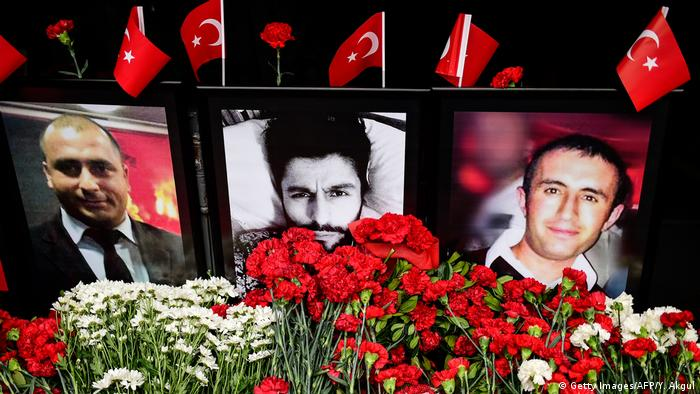 Flowers along with portraits of three of the victims of the Reina attack.