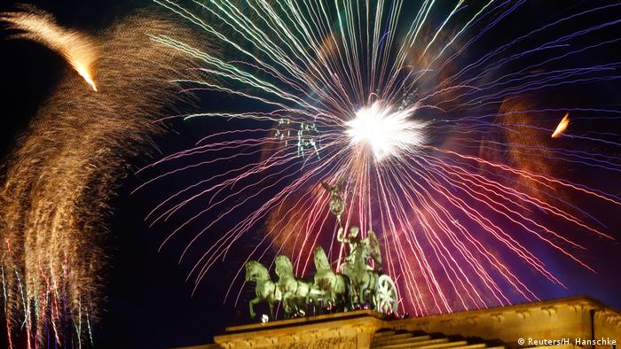 fireworks explode above the brandenburg gate in berlin